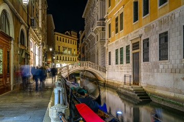 Wall Mural - Narrow canal with gondola and bridge in Venice, Italy. Architecture and landmark of Venice. Cozy night cityscape of Venice.