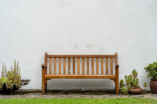 Wooden bench front of a white wall