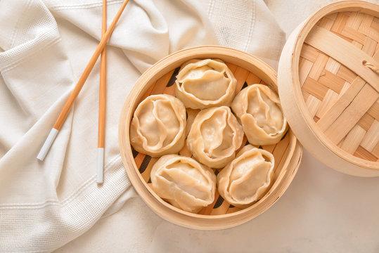 Steamer with oriental dumplings on white background