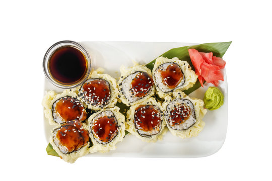 Sushi, rolls, uramaki, tempura with teriyaki sauce, sesame, raw seafood, soy sauce, marinated ginger and wasabi. Food on a banana leaf, on plate, white isolated background, view from above