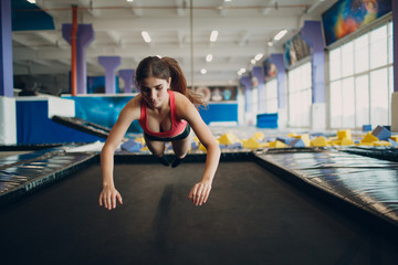 Young woman acrobat learns to jump on a trampoline.