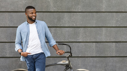 Handsome black man standing with bike against urban wall, looking away Fotobehang