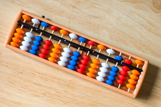 Mental arithmetic and development concept, abacus and mathematical examples on a wooden background