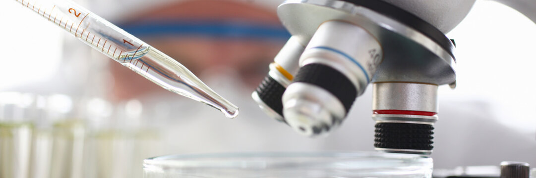 Scientist dosing a drop with pipet to exam with microscope
