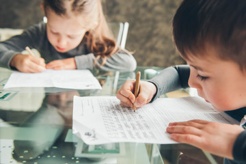 Schoolboy and schoolgirl writing letters. Close-up  pencil in the hand of child. Children learning to write letters at the table.