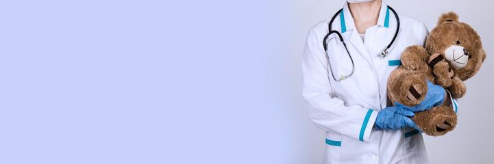 Female doctor pediatrician holding a teddy bear