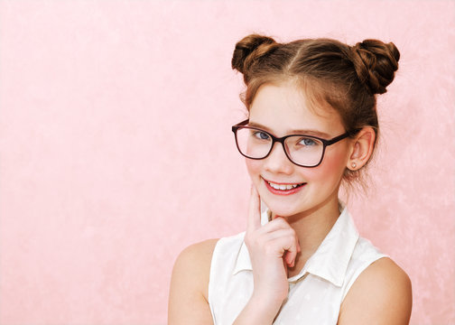 Portrait of funny smiling little girl child wearing glasses isolated on a pink