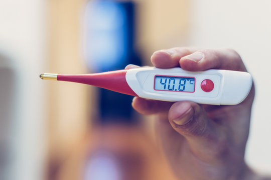 Flu and corona concept: Man is holding a fever thermometer in his hand, close up
