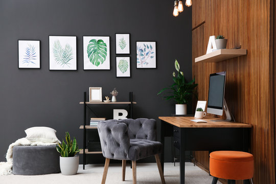 Comfortable workplace with computer near wooden wall in stylish room interior. Home office design