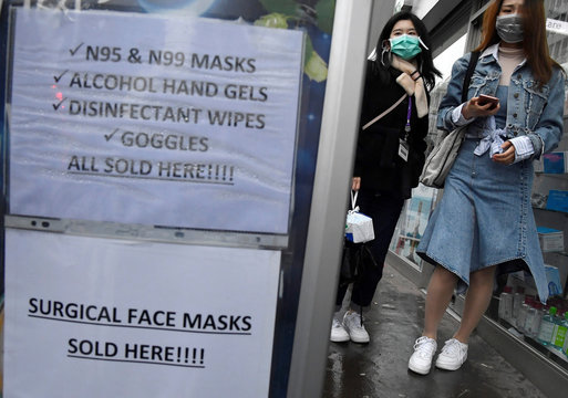 Customers wearing protective face masks are seen leaving a pharmacy in London