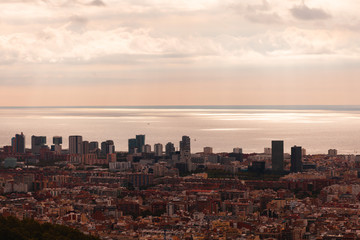 Elevated view of crowded cityscape with sea in background at sunset, Barcelona, Spain