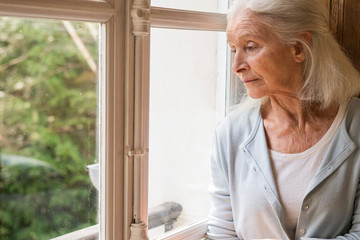 Sad senior woman looking through window