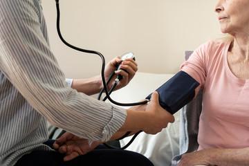 Home carer checking blood pressure of senior woman at nursing home