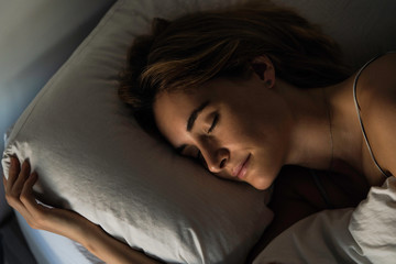 Close-up of young woman sleeping peacefully on bed in bedroom