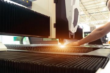 Man controls laser cutting of metal