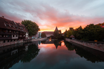 View of old buildings and bridge reflected in water during sunset, Nuremberg, Germany