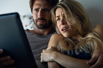 Young couple watching horror movie on digital tablet in bedroom