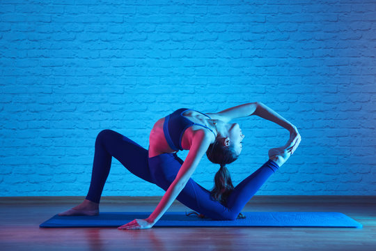 Flexible plastic girl doing pilates exercises on mat in yoga studio, body stretching pose