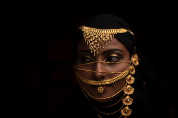Conceptual middle eastern face portrait of a woman adorned with golden jewelry in black studio background.  conceptual model photography.