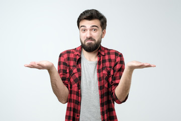 Confused hispanic man giving I dont know gesture on white background.