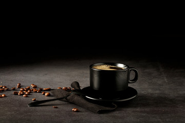 Black coffee cup with coffee on a dark background. With copy space for your text. Cup of coffee on a black background low key copy space.