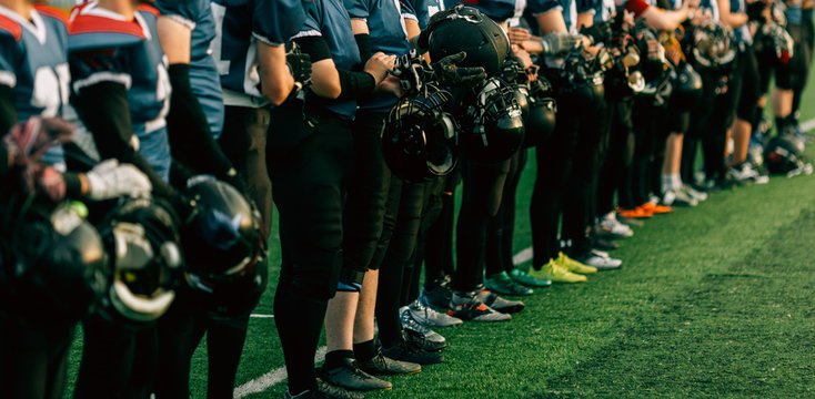 American football team with football helmets standing in football field