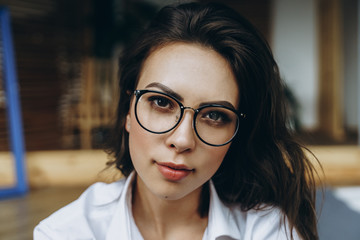 Portrait of happy woman wearing eyeglasses and looking at camera