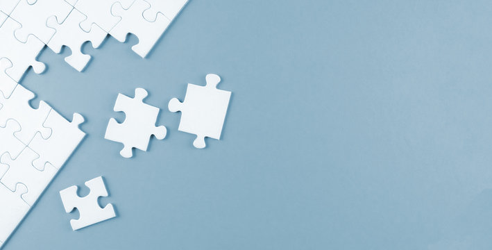 top view of white blank unfinished jigsaw puzzle on blue background, completing a task or solving a problem concept