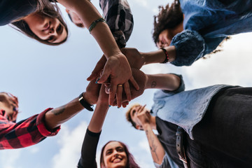 Many hands together: group of people joining hands.
