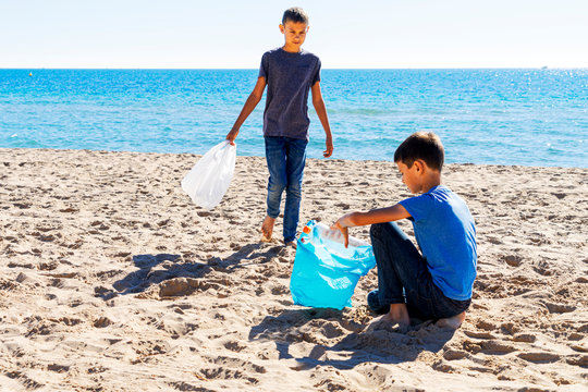 Volunteers cleaning beach from plastic. Boys walking on the beach and picking up plastic bottles trash and putting into plastic bag for recycle