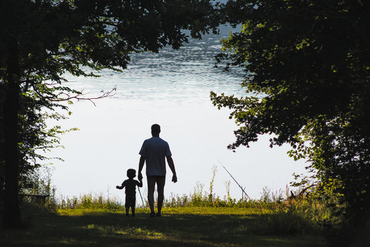 Anonymous father and child relaxing at the lake