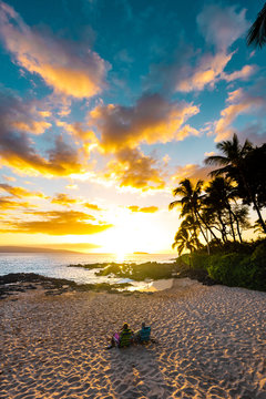 Couple on Vacation Sitting Relaxing on Beach in Lazy Chairs on Sandy Sea Shore Watching A Colorful Sunset Sky Surrounded By Palm Trees and Clear Blue Ocean in Tropical Island Paradise of Maui Hawaii
