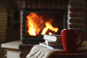 Books and cocoa on table near burning fireplace, space for text. Reading at home Fotobehang