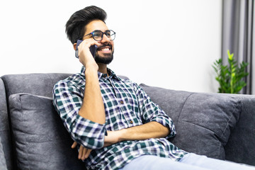Young indian man talking on the phone while sitting on a couch