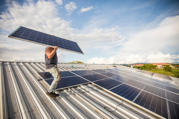 Man carrying solar panel, installing on roof.