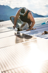 Worker uses hand tool to secure solar panels on roof of building.