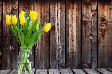 Bunch of bright yellow spring tulips in a glass container on a rustic plank table.