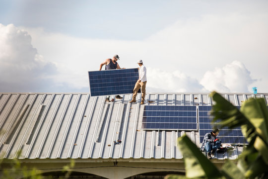 Team of electricians work to install solar panels on rooftop.