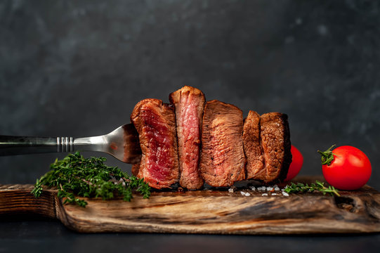 four steaks on  fork on a cutting board on a stone background.Four types of meat frying Rare, Medium, Medium Well, Well Done