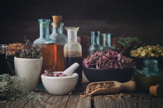 Bottles of healthy tincture or infusion, mortar and bowls of medicinal herbs on table. Herbal medicine.