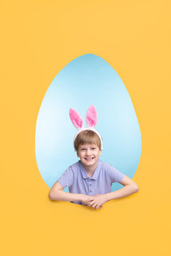 Portrait of happy excited boy in ear hare headband standing in Easter egg-shaped frame