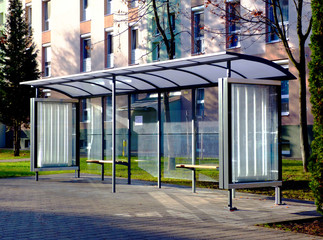 Fototapeta clear glass and aluminum frame structure bus shelter at bus stop in residential area. bare trees and green grass in the background. public transportation. ad and copy space. obraz