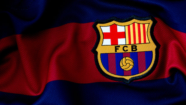 London, UK - February 15 2019:Illustrative editorial of a macro close up of a soccer jersey on the football club Barcelona logo with dramatic lighting and copy space