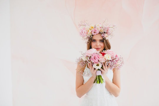 Portrait of beautiful bride with flower wreath on her head and bridal bouquet