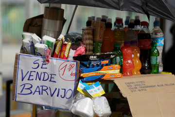 """A sign that reads """"Masks are sold here"""" hangs at a vendor's cart right next to protective face masks, at the Bus Terminal of La Paz"""