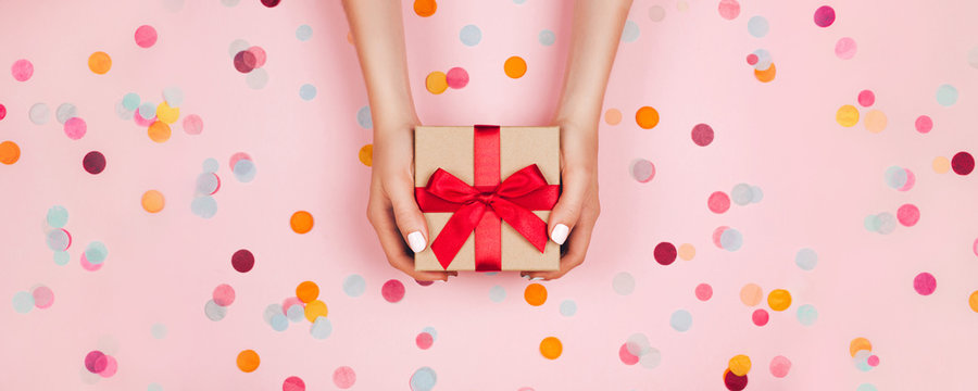 Banner. Woman hands holding present box with red bow on pastel pink background with multicolored confetti. Flat lay style.
