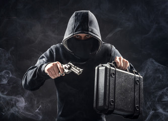 Man in black hoodie with gun and suitcase. Bank robbery. Criminal drug dealer concept.
