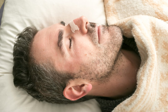 Man sleeping in bed using a nasal strip. External nasal dilator strip is a type of adhesive bandage with embedded plastic ribs or splints that is applied across the bridge of the nose
