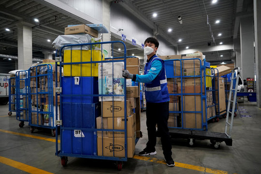 A delivery man for Coupang Jung Im-hong wearing a mask to prevent contracting the coronavirus, loads packages before leaving to deliver them in Incheon