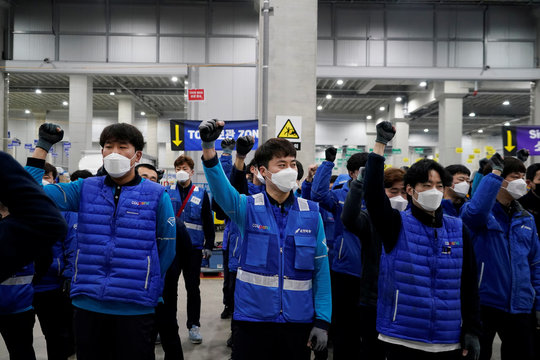 A delivery man for Coupang Jung Im-hong wearing a mask to prevent contracting the coronavirus, shouts slogans before leaving to deliver packages in Incheon